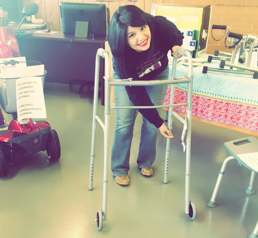 Laura Sagredo, owner of Glorious Medical Equipment, LLC, adjusting a walker.